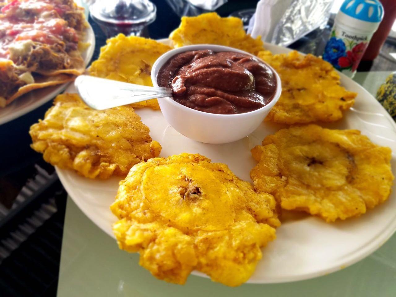 Plat de patacones (plantins frits) servis avec une trempette d'haricots (frijoles)